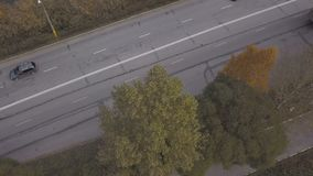 Drone view trucks and cars moving on highway road on background autumn nature. Car moving on suburban road through autumn forest stock video footage