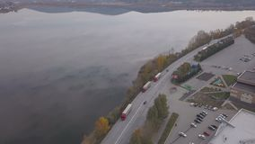 Drone view trucks and cars moving on road on background industrial area in city. Truck cars with freight container driving on highway through river embankment stock video footage