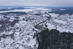 Drone view of winter forest, curving river and small village royalty free stock images