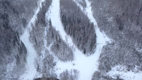 Drone view winter skiing and snowboarding on ski slope in winter resort. Ski lift on snow mountain at ski resort in winter forest aerial view. Winter stock video