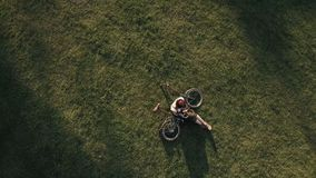 Drone view woman cyclist lying on green grass and using mobile phone. Young woman resting in city park and holding smartphone on background bike on lawn. Woman stock footage