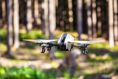 Drone in the wild. A small spy quad copter scout drone flying through the trees in a forest stock photography