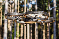 Drone in the woods. A small spy quad copter scout drone flying through the trees in a forest stock photos