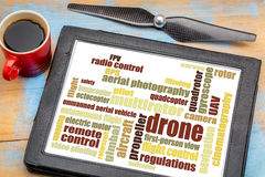 Drone word cloud on digital tablet. Drone word cloud on a digital tablet with a cup of coffee and a drone propeller against a grunge painted wood stock photos