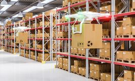 Drone at work in warehouse. Modern drone carries a cardboard package between the aisles of a warehouse. 3d render image. Automated logistics concept stock photography