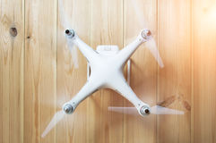 Drone in a working mode on a wooden background. Whirling blades. stock images