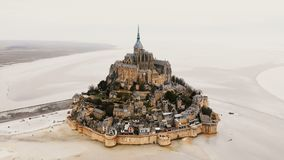 Drone zooming in on Mont Saint Michel abbey, epic island fortress town and famous travel landmark in Normandy France.