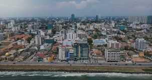 Drone zooming out above Colombo, Sri Lanka panorama. Aerial view of Asian resort town, modern buildings and ocean waves. Beautiful scenery of architecture stock video