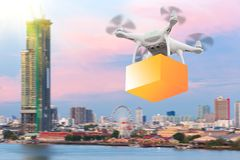Drones flying through the air in sunset sky with a cardboard box. Package carrying clamped to send for customer. Futuristic delivery drone concept royalty free stock photo