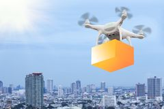 Drones flying through the air in sunset sky with a cardboard box. Package carrying clamped to send for customer. Futuristic delivery drone concept stock photography