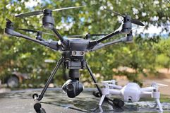 DRONES - Large & Small Camera UAV / UAS. Two drones, a large hexacopter and a smaller portable quadcoter Stock Images
