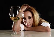 Dronken alcoholische blonde vrouw alleen in verspild gedeprimeerd het drinken wit wijnglas die aan kater lijden Royalty-vrije Stock Foto