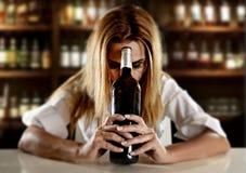 Dronken alcoholische blonde vrouw alleen in verspilde gedeprimeerd met rode wijnfles in bar stock afbeelding
