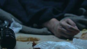 Dronken bedelaar die die in huisvuil liggen, met alcohol wordt bedwelmd, die aan pijnlijke plekken op hand lijden stock footage