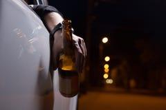 Dronken jonge mens die een auto met een fles bier drijven Trek de Drank en de Aandrijvingsconcept aan van ` t Het drijven onder d royalty-vrije stock afbeelding