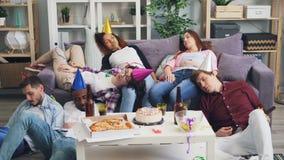 Dronken jongerenmannen en vrouwen die op bank en vloer na partij thuis slapen stock footage