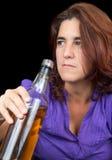 Dronken Latijnse vrouw die een whsky fles houdt stock afbeelding