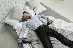 Dronken mannelijke persoon op bed stock afbeelding