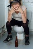 Dronken meisje in een openbaar toilet Stock Foto's