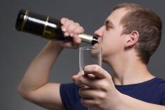 Jonge gedronken mens met fles alcohol en glas stock afbeeldingen