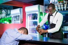 Dronken mensenslaap met zijn hoofd op barteller Royalty-vrije Stock Fotografie
