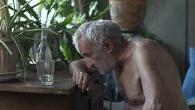 Dronken oude mensenslaap bij de lijst stock videobeelden