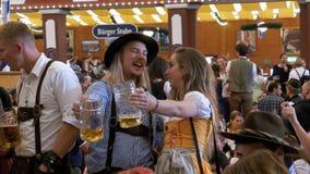 Dronken vrouw en man met een mok bier dat Oktoberfest binnen een grote biertent viert Beieren, Duitsland stock videobeelden