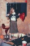 Dronken vrouw in slordige ruimte na partij stock afbeelding