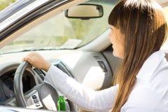 Dronken vrouwelijke automobilist die aangezien zij drijft grijnzen Stock Foto