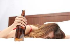 Dronken vrouwenslaap op bed met binnen fles van wijnstok Stock Foto's