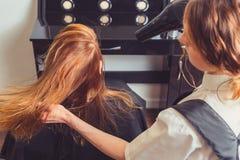Droog de vrouwen` s haar van de schoonheidsspecialistslag bij schoonheidssalon royalty-vrije stock foto's