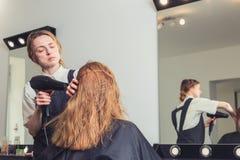 Droog de vrouwen` s haar van de schoonheidsspecialistslag bij schoonheidssalon stock foto