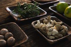 Droog gember, notemuskaat en rozemarijnkruid in een kom stock foto's