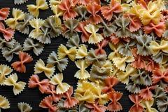 Droog hierboven gekleurde farfalle deegwaren op zwart geweven hout van A Stock Fotografie