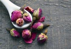Droog nam knoppenbloemen in een witte lepel op oude houten lijst toe Aziatisch ingrediënt voor aromatherapy aftreksel stock foto