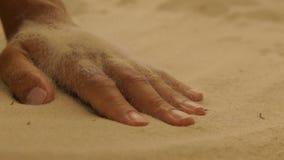 Droog overzees zand op een vrouwen` s hand stock footage