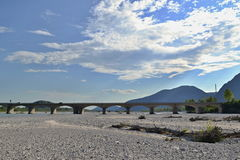 Droog rivierbed met brug, blauwe hemel en wolken op achtergrond Stock Fotografie