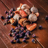 Droog rozebottels, okkernoot en gedroogd fruit op een houten raad Royalty-vrije Stock Afbeelding