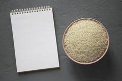 Droog witte rijst basmati in een roze kom, lege blocnote over grijze achtergrond, hoogste mening Vlak leg hierboven, overheadkost royalty-vrije stock fotografie