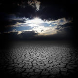 Droogtebarsten en donkere hemelwolken Stock Afbeelding