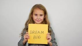 Droom grote uitdrukking op geel document Het glimlachen de slogan van de meisjesholding stock video