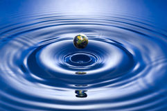 Drop. Earth drop on blue background close up shoot Royalty Free Stock Photo