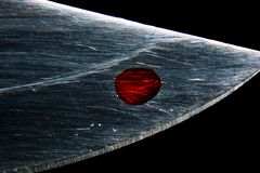 A drop of blood on the blade of a knife macro stock image