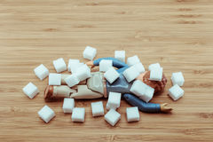 Drop Dead doll man under falling sugar cubes. For the concept of high blood sugar, obesity, diabetic Royalty Free Stock Photo