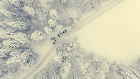 Drop down of a road through snow covered forest. Winter landscape from above Royalty Free Stock Images