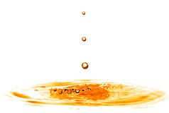 Drop falling into orange water with splash isolated on white Stock Images