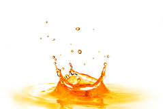 Drop falling into orange water with splash isolated on white Stock Image