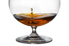A drop falls in glass with cognac Royalty Free Stock Image