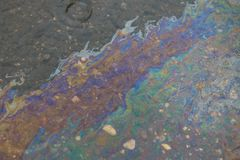 A drop of gasoline in a puddle, on a wet asphalt, spreads in the form of a larger poisonous stain. Spilled gasoline in a puddle, on a wet asphalt, spreads in the royalty free stock photo