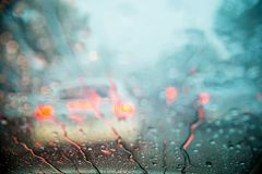 Drop on glass at twilight time while raining.View side out the car.Rain drops on window with road light bokeh,. City life in rainy season abstract background stock photo